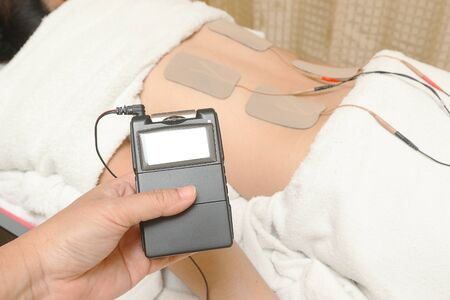 physiotherapists: TENs therapy, Electrodes of tens device on back muscle