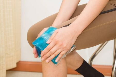 knee: woman applying cold pack on swollen hurting knee after sport injury
