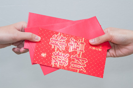 envelop: woman hand giving red envelop containing money, with Good Luck character, during Chinese New Year celebration