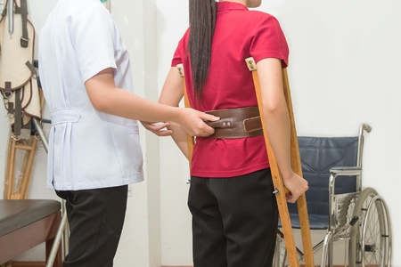 ambulatory: Physical therapist helping patient to walk using crutches  in hospital, physical rehabilitation therapy