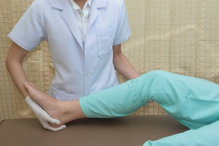 knee: Patient doing knee exercises with physical therapist , in rehabilitation clinic
