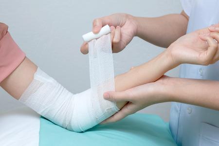 elbow bandage support: Nurse applying bandage to patient injured elbow Stock Photo