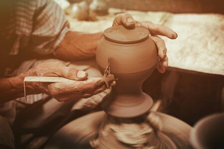 potter: Potter makes on the pottery wheel clay pot.