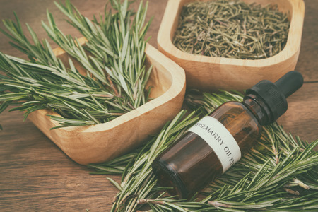 Rosemary essential oil in bottle and fresh rosemary on old wooden background Standard-Bild