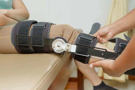 Orthopedist secures leg brace on knee, knee brace support for leg or knee injury