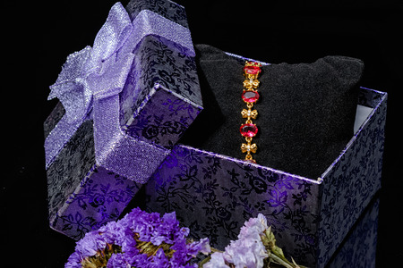 jewlery: Ruby gold bracelet in gift box isolated on black background