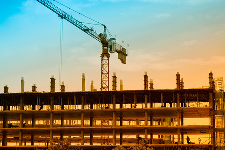 concrete commercial block: Construction site with crane and building at sunset