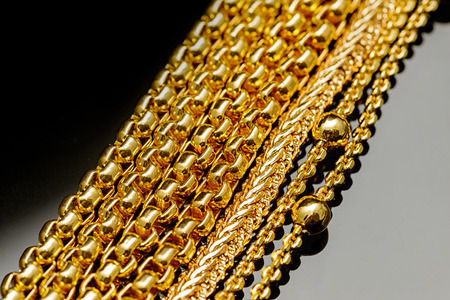 gold chain: Closeup gold chain necklaces over black background