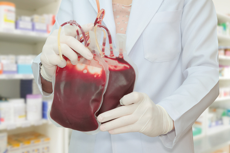 transfused: Doctor holding fresh blood bag for transfusion ,Blood donation concept Stock Photo