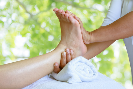 Masseur doing reflexology,Thai foot massage in spa on nature background