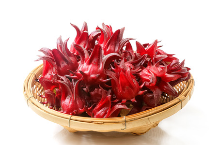 Roselle fruits in bamboo basket, isolated on white