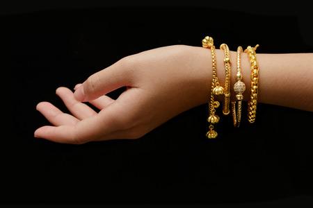 Hand der Frau mit vielen verschiedenen goldenen Armbänder auf schwarzem Hintergrund