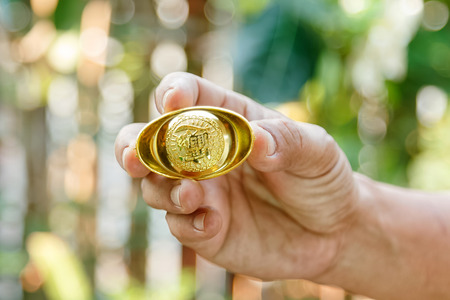 futures: Hand giving gold ingot to someone for Chinese New Year celebration on red background