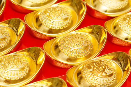 ingots: Gold ingots of China in the Chinese New Year festive on red Background. Stock Photo