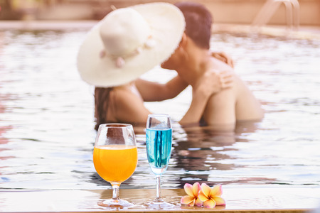 Romantic Asian couple kissing in the swimming pool with cocktail (Focus on cocktail )