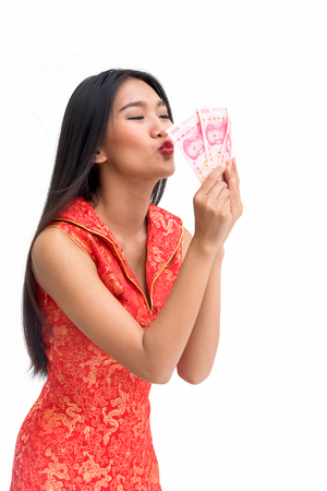 carreer: Smiling Chinese woman in red dress kiss some of bank notes in hand Stock Photo