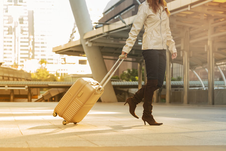 Asian woman carry suitcase travel alone in the city. Stock Photo