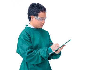 protective clothing: Asian surgeon man with protective clothing filling the medical record,medical and health care concept Stock Photo