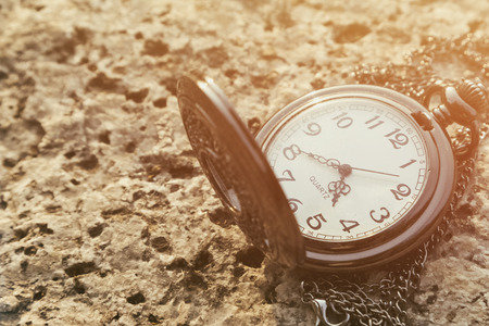 timekeeping: Antique pocket watch against the background of dried leaves  Stock Photo