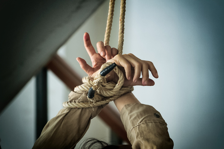 human hands tied up together with rope
