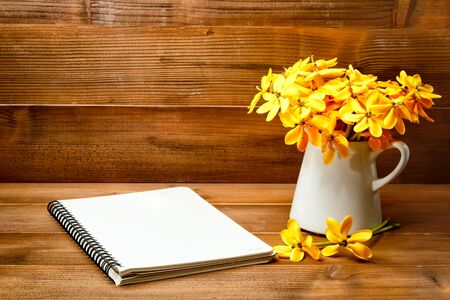Yellow gardenia flower in vase with note book on wooden background with copy space.