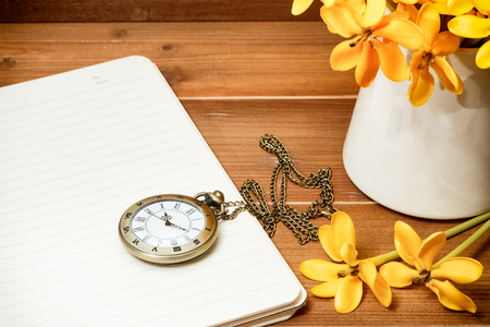 Antique pocket watch with yellow gardenia flower on wooden background Stock Photo
