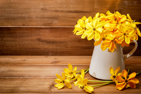 yellow gardenia flower in vase on wooden background with copy space