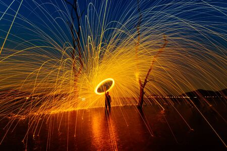 steel wool: Burning Steel Wool spinning,Circle fire at sunset Stock Photo