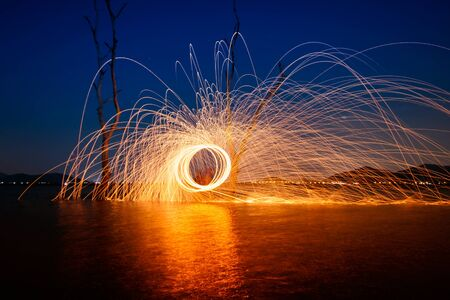 steel wool: Ring of fire at the lake,still wood light Stock Photo