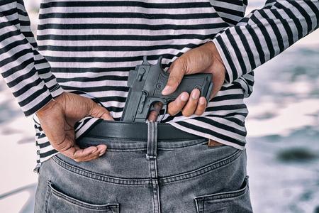 Closeup murder hidden gun behind his back Stock Photo