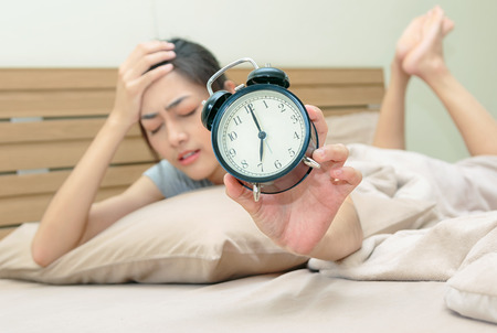 Sleepy young woman in bed with eyes closed extending hand to alarm clock at home