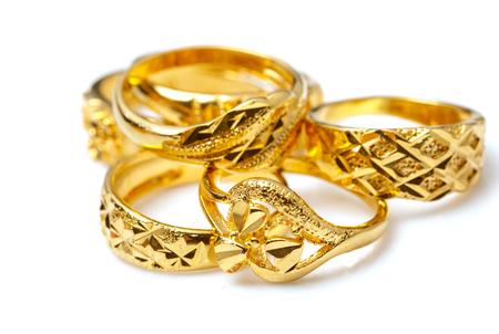 Grupa wielu projektowych złotych pierścionków na białym tle