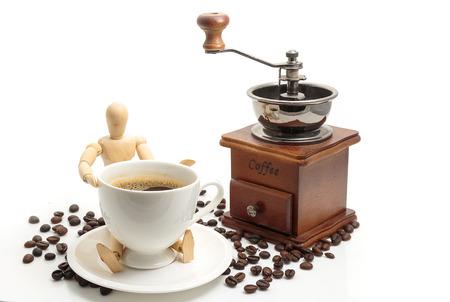 ビンテージ木製コーヒー グラインダー コーヒー豆と白い背景があるコーヒー カップ