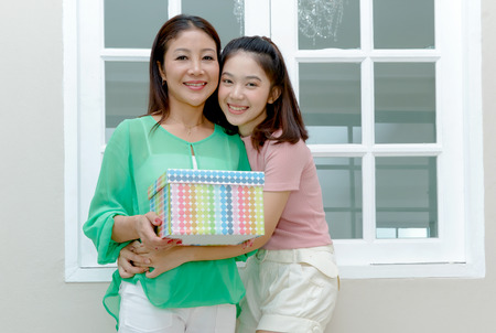Joyful Asian mother and teenage girl holding gift box and smile,mother day