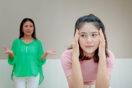 화가 난 어머니가 뭔가 불평하는 딸 뒤에 서있다.