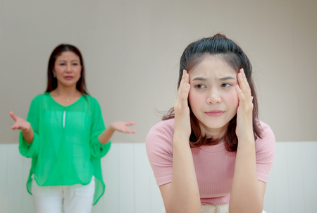 Angry mother stands behind her daughter complaining something Foto de archivo