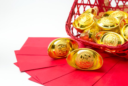Chinese new year ornaments, red packets, gold ingots on white background Stock Photo