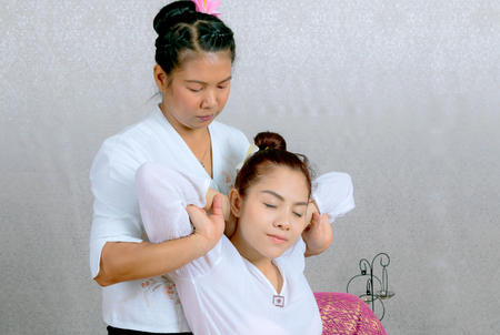 Asian woman getting traditional thai stretching massage by therapist
