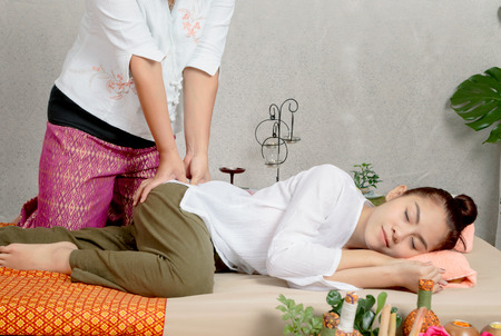 Traditional thai massage, woman getting thai deep massage in spa