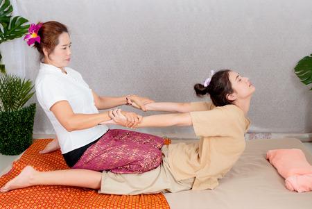 Aziatische vrouw die traditionele Thaise uitrekkende massage krijgt door therapeut Stockfoto