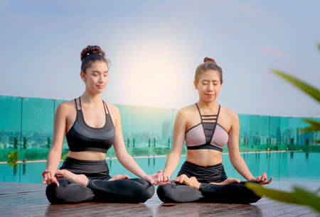 Yoga beautiful women meditating in lotus pose at terrace city scape background Stock Photo