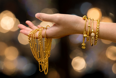 woman hand hold gold bracelet and necklace  jewelry Archivio Fotografico
