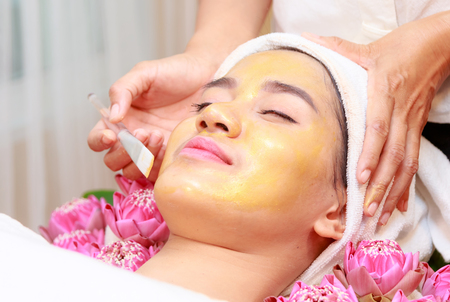 Happy relax woman getting gold facial mask at beauty salon.