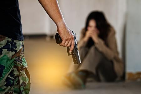 총에 의해 그녀를 위협하는 범인에 의해 납치 된 여성.