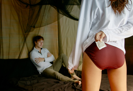 Back view of sexy woman holding a condom while her boyfriend is lying on bed