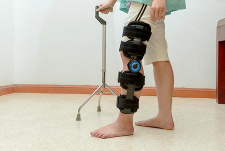 splint: Mujer caminando con muletas, con soporte de rodilla en el centro de rehabilitación