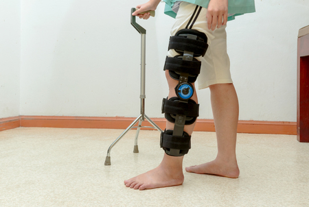Woman walking on crutches, wearing knee support in rehab center Stockfoto