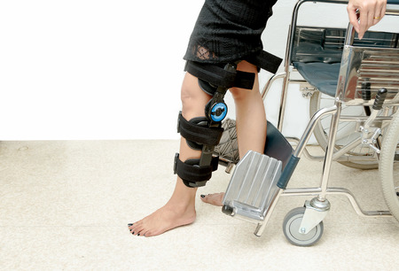 Patient on knee brace support try to walk training,Rehabilitation treatment Фото со стока - 88147679