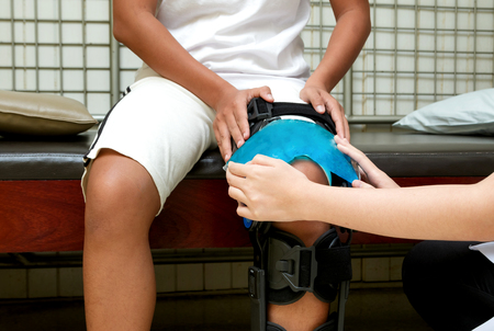 Physical therapist applying cold compress on patient knee to reduce pain