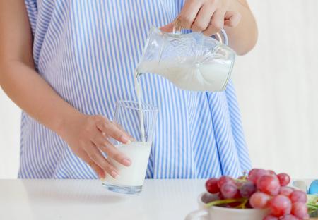 Auslaufende Milch der schwangeren Frau der Junge, gesunde Nahrung während der Schwangerschaft Standard-Bild